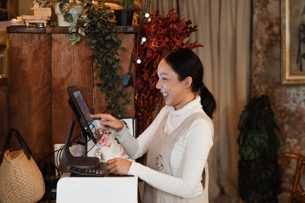 Exited ethnic waitress working with cash desk in cozy cafeteria